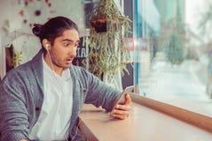 Verraste mens die zijn telefoon bekijken stock fotografie