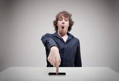 Verraste mens wat betreft het zijn smartphonescherm royalty-vrije stock afbeeldingen