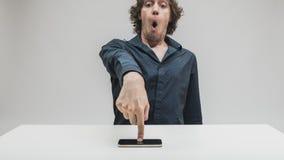 Verraste mens wat betreft het zijn smartphonescherm stock foto's