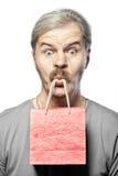 Verraste rijpe geïsoleerde mens met het winkelen zak in mond royalty-vrije stock afbeeldingen