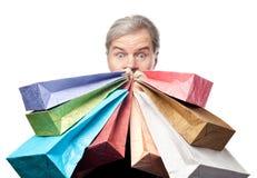 Verraste rijpe mensenholding het winkelen zakken dichtbij geïsoleerd gezicht royalty-vrije stock fotografie