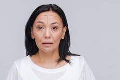 Verraste schitterende vrouw die een plooi op chirurgie plannen Royalty-vrije Stock Foto