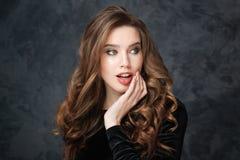 Verraste tedere jonge vrouw met mooi krullend haar stock foto