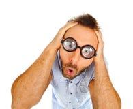 Verraste uitdrukking van een jonge mens met dikke glazen Stock Afbeeldingen