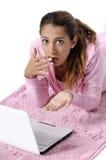 Verraste vrouw die achterwaarts met laptop kijkt Royalty-vrije Stock Foto