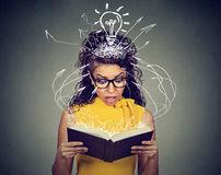 Verraste vrouw die die een boek lezen door een onverwachte perceeldraai wordt gefascineerd royalty-vrije stock foto's