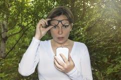 Verraste vrouw die telefoon bekijken Stock Foto's