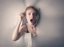 Verraste vrouw die uit van een wit karton knallen Stock Afbeelding
