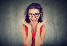 Verraste vrouw in glazen over grijze achtergrond stock afbeeldingen