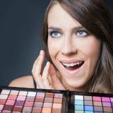 Verraste vrouw met kleurrijk palet voor maniermake-up Royalty-vrije Stock Afbeeldingen