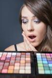 Verraste vrouw met kleurrijk palet voor maniermake-up Royalty-vrije Stock Afbeelding