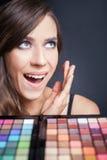 Verraste vrouw met kleurrijk palet voor maniermake-up Royalty-vrije Stock Fotografie