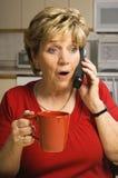 Verraste vrouwenbesprekingen op telefoon Royalty-vrije Stock Foto
