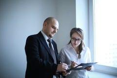Verraste zakenman en medewerker die bedrijfsdocumenten bespreken royalty-vrije stock afbeelding