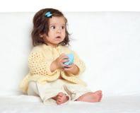 Verraste zeer weinig kindmeisje zitten op witte handdoek Emotie en gezichtsuitdrukking Stock Foto's