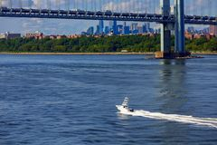 Cabin Cruiser Under Verrazano Bridge with Manhattan in the Backg. The Verrazano-Narrows Bridge spanning Staten Island and Brooklyn New York Royalty Free Stock Photography