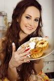 Verrückte Hausfrau auf dem lächelnden Essen der Küche Lizenzfreie Stockbilder