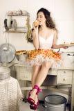 Verrückte Hausfrau der wirklichen Frau auf der Küche, essend Lizenzfreie Stockfotografie