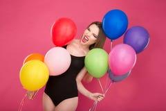 Verrückte schreiende junge Frau, die mit bunten Ballonen pozing ist Stockfotografie