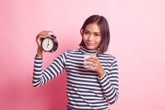 Verre à boire asiatique sain de femme d'horloge de prise de lait photographie stock libre de droits
