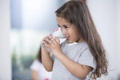 Verre à boire mignon de fille de l'eau à la maison Image libre de droits