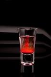 Verre à liqueur rouge sur un fond foncé images stock
