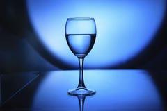 Verre à vin avec de l'eau sur le fond clair en verre et bleu Image libre de droits
