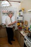 Verre à vin de nettoyage d'homme plus âgé Photographie stock libre de droits