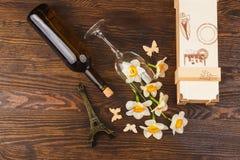 Verre à vin et bouteille avec les fleurs et les papillons décoratifs Image libre de droits