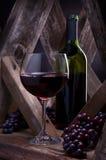 Verre à vin et bouteille dans un arrangement rustique de cave. photos libres de droits