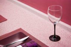 Verre à vin, plat et serviette vides sur le dessus de table préparé pour le déjeuner ou le dîner dans la couleur rose photographie stock libre de droits