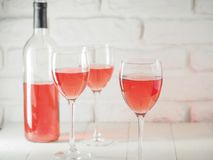 Verre à vin trois avec du vin rose et la bouteille sur le fond blanc de mur de briques Image libre de droits