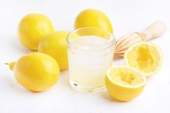 Verre AR de limonade fraîche savoureuse froide avec le presse-fruits en bois de citrons mûrs photo libre de droits