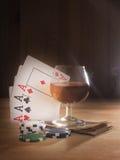 Verre avec de l'alcool, jouant des cartes Fond en bois Images stock