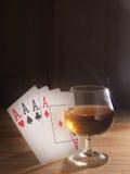 Verre avec de l'alcool, jouant des cartes Fond en bois Photos libres de droits