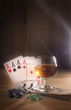 Verre avec de l'alcool, jouant des cartes Fond en bois Photo libre de droits