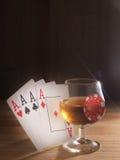 Verre avec de l'alcool, jouant des cartes Fond en bois Photographie stock