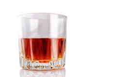 Verre avec de l'alcool sur un fond blanc avec la réflexion photos stock