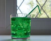Verre avec de l'eau aéré par soude verte Image libre de droits