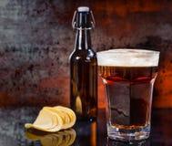 Verre avec de la bière foncée fraîchement versée, bouteille à bière près dispersée photos libres de droits