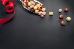 Verre avec des dragées de chocolat pour le jour de valentines Image libre de droits