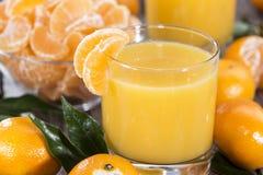 Verre avec du jus de mandarine Photographie stock libre de droits