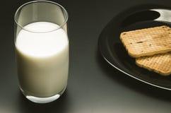 Verre avec du lait et des biscuits dans un plat sur un fond noir Image libre de droits