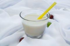 Verre avec du lait sur un fond blanc Photographie stock