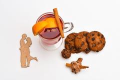 Verre avec du vin chaud avec le biscuit et la silhouette en bois des couples dans l'amour, fond blanc Vin chauffé avec des biscui Photos stock