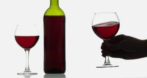 Verre avec du vin ros? Verres de vin avec le vin rouge sur le fond blanc banque de vidéos