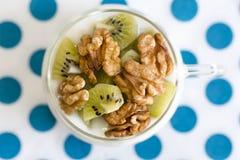 Verre avec du yaourt simple avec le kiwi et les écrous Photos stock