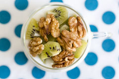 Verre avec du yaourt simple avec le kiwi et les écrous Photographie stock libre de droits