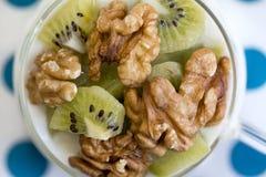 Verre avec du yaourt simple avec le kiwi et les écrous Images stock