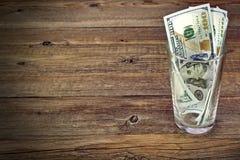Verre avec l'argent pour la grande astuce avec des billets d'un dollar Photographie stock